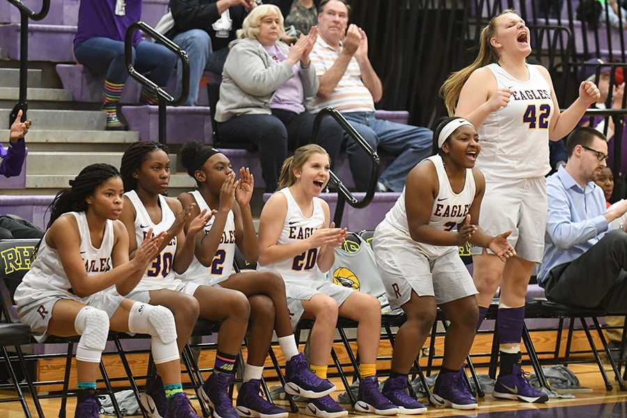 The girls varsity basketball team cheers during a successful game against Coppell last Friday. Photo by Madison Staggenborg