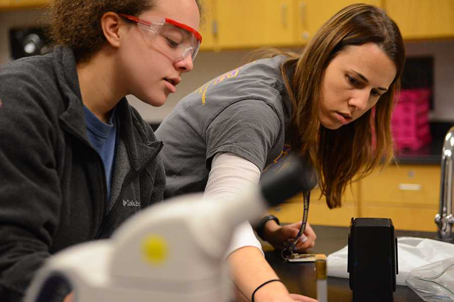 Teacher Allia Shelby reaches over to help senior Brighton Harding with her forensics lab. Photo by Collin Grant