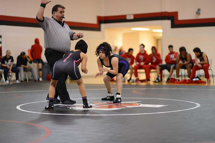 Senior Erika Torres crouches in preparation to defeat her opponent at a wrestling match. Photo by Alisia Cabrera