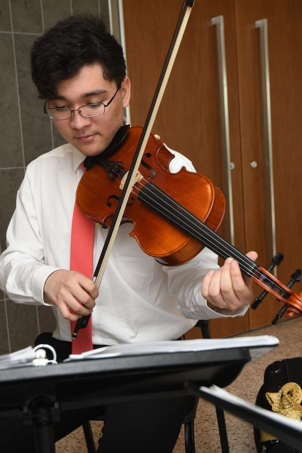 Senior Ricky Maasz plays in the lobby of the auditorium as part of the 4 Man Trio. Contact the group at thefourmantrio@gmail.com for booking purposes. Photo by Chad Byrd