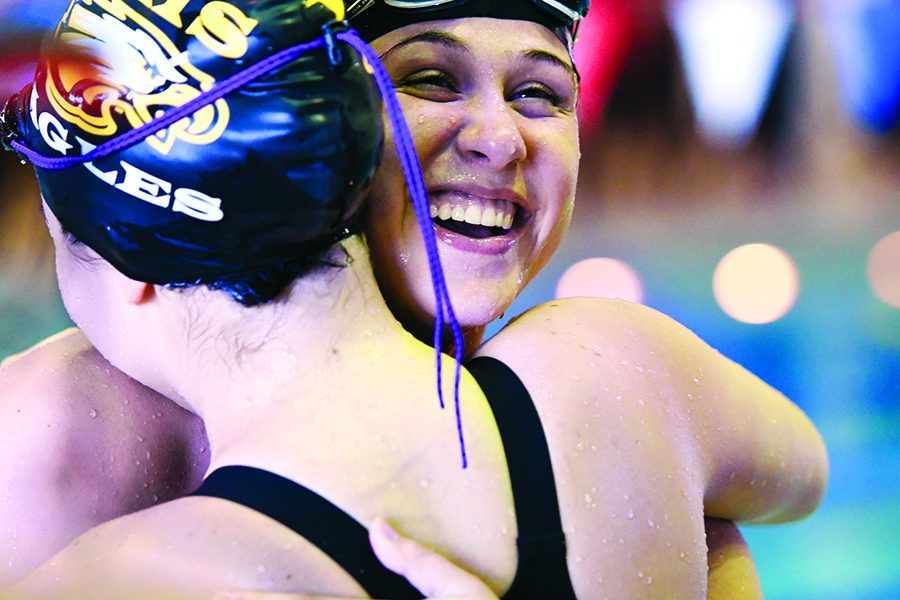 Senior Hailey Falies embraces a teammate after discovering her swim time. Photo by Travis Pokorney
