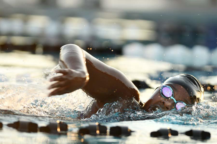 Junior Shiko Kimyanjui swims the freestyle race during the mesquite swim meet at dusk