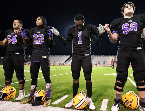 Varsity football players Kain Perez, Michael Gilmer, Stone Carter and Drew Moss stand for the alma mater after losing the final game of the season to Lake Highlands. Photo by Chad Byrd Photo credit: Chad Byrd