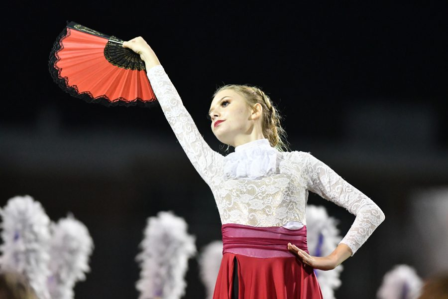 "During the band's halftime show ""Danza De La Rosa"" which was thought of last year when sophomore Brian Gary would dance to salsa music every morning, freshman Kiran Scarth strikes a pose. This was the first year colorguard used handheld props other than flags in their performance. Talon photo by Daphne Lynd"