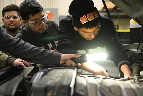 Senior Esgar Angel works on car during first period auto tech class. Photo by Chad Byrd