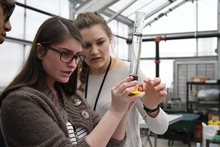 """Seniors Alexis Koladycz and Sarah Jackson measure soil in the new greenhouse. """"We were trying to determine the quality of the soil,"""" Koladycz said."""